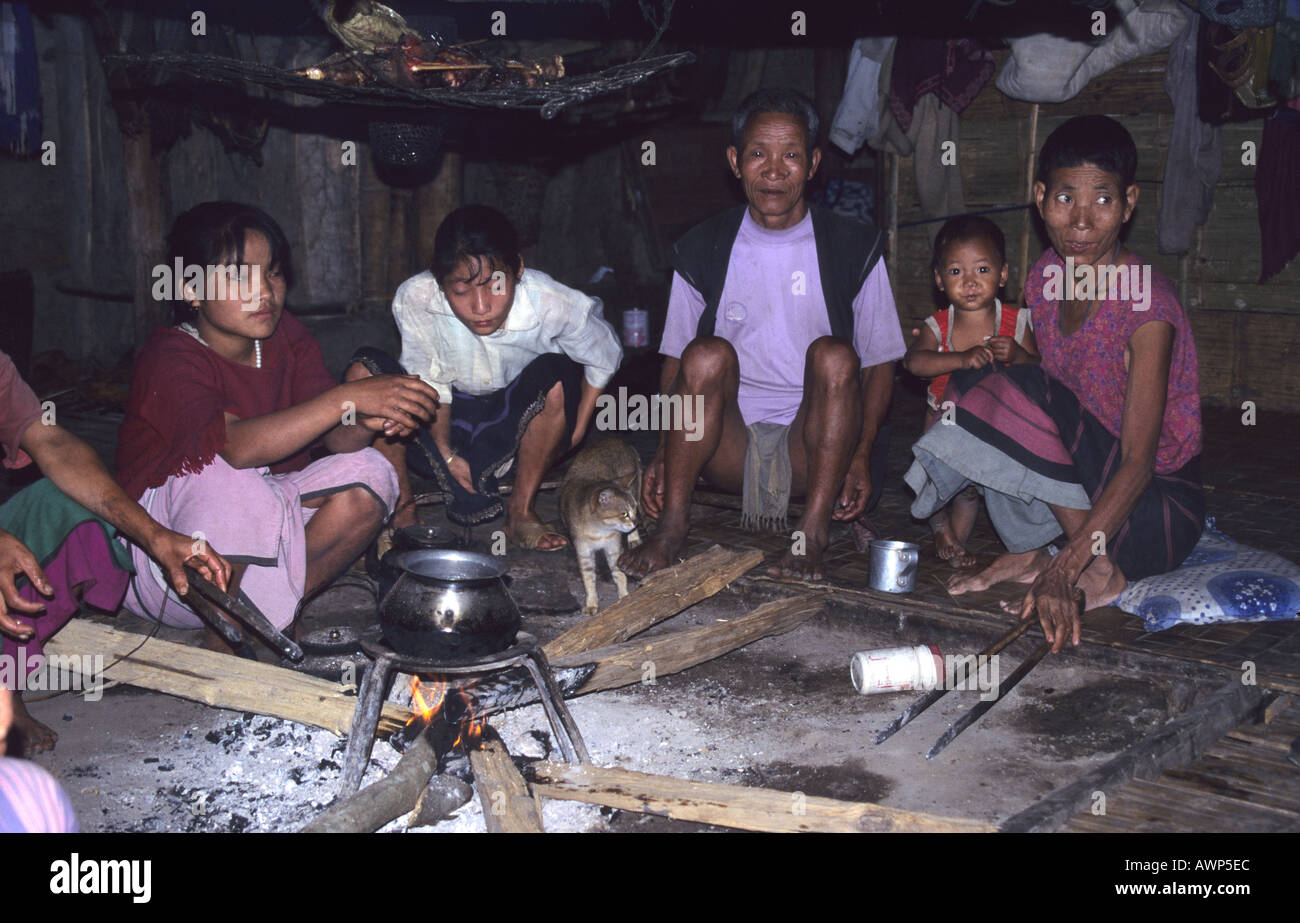 Members of the Apatani tribe sitting around a fire in a typical 'long house homestead ' Araunacal Pradesh ,N India - Stock Image
