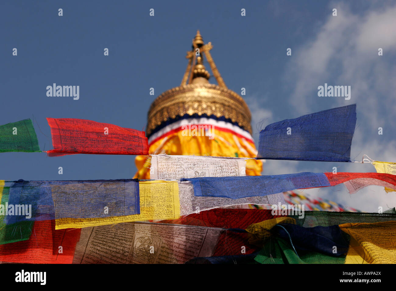 Red, yellow, white, blue and green prayer flags at the Bodnath stupa, accompanied by traditional Tibetan prayer - Stock Image