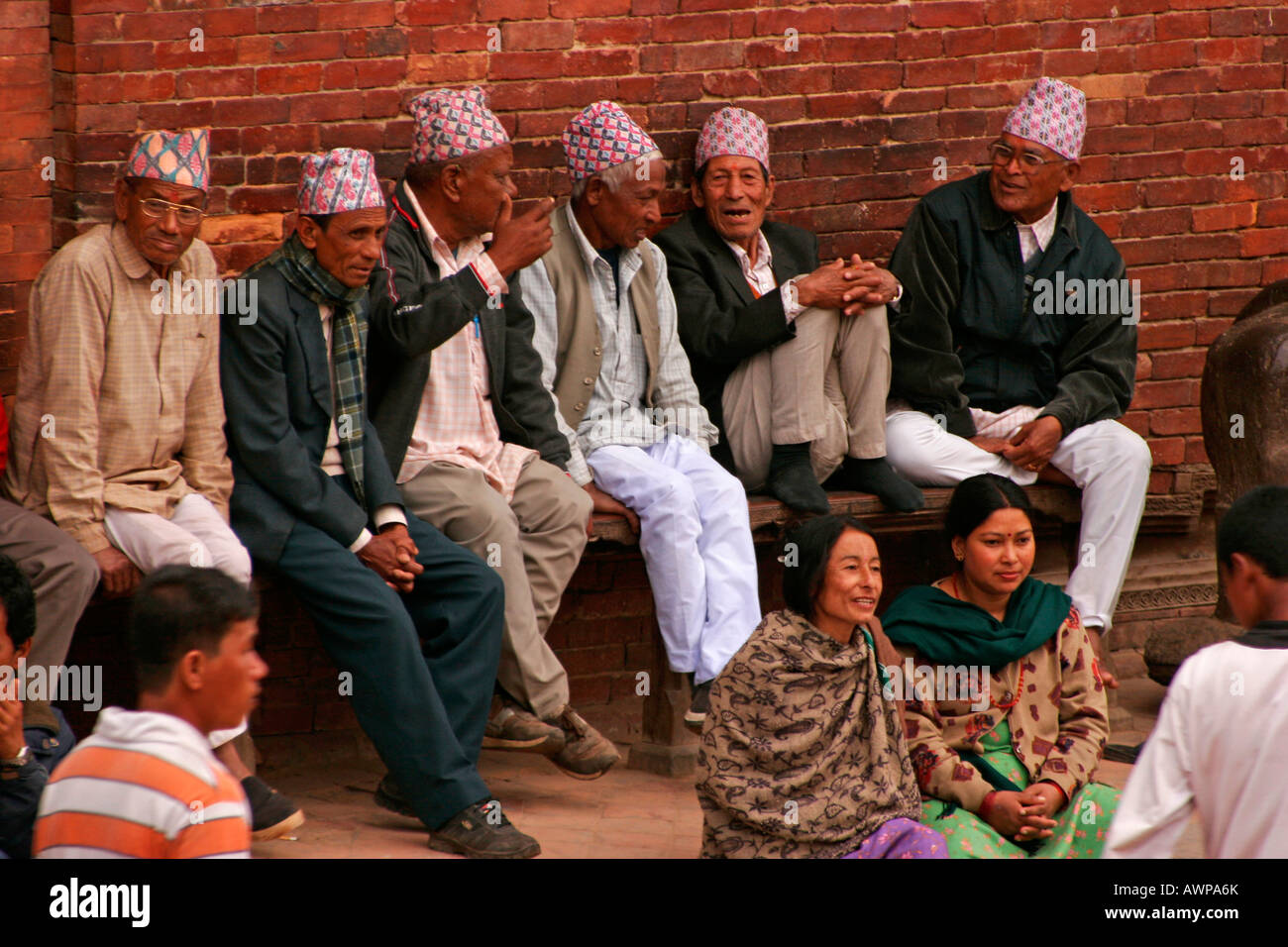 Six elderly gentlemen wearing typical Nepalese head coverings called 'topi' sitting on a bench chatting, - Stock Image