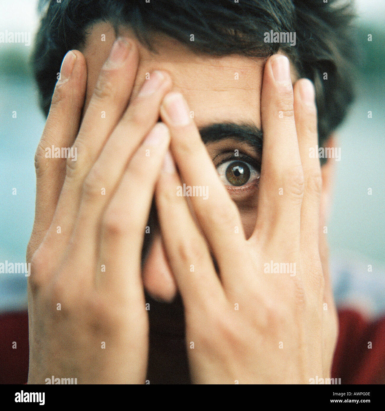 Young man with hands over face, looking through fingers with one eye, close-up - Stock Image