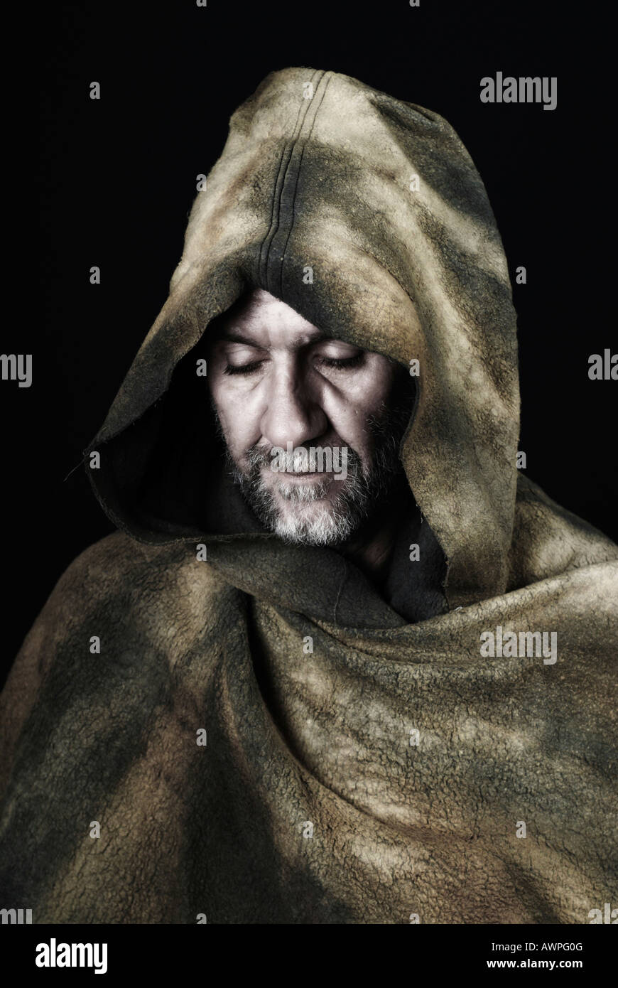 Hooded monk wearing cloak - Stock Image