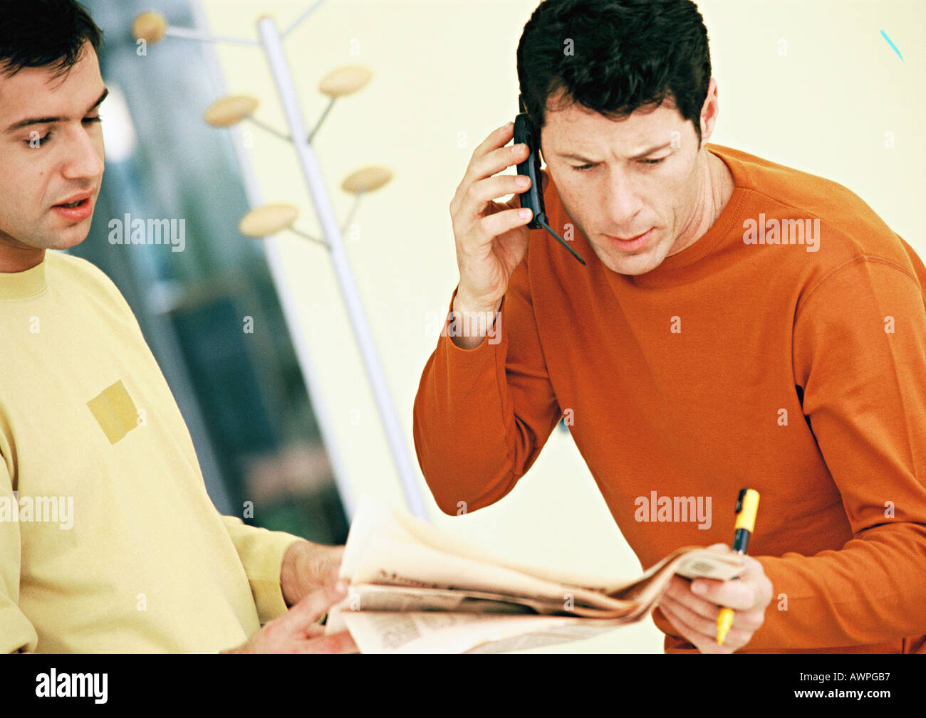 Men looking at newspaper, one using cell phone Stock Photo