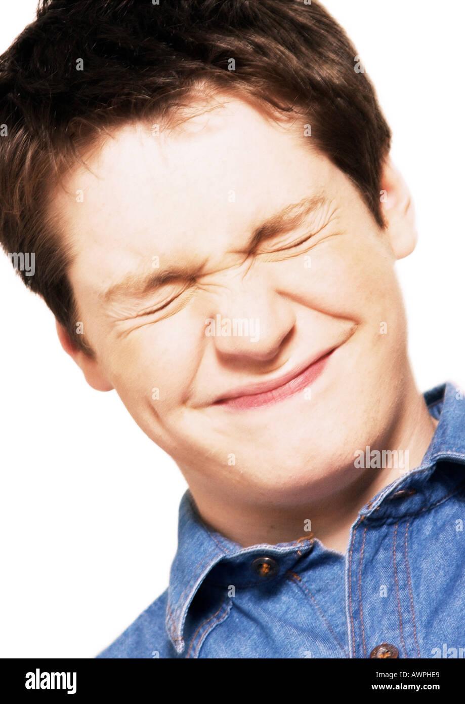 Teenage boy squinting eyes shut, close-up, portrait - Stock Image