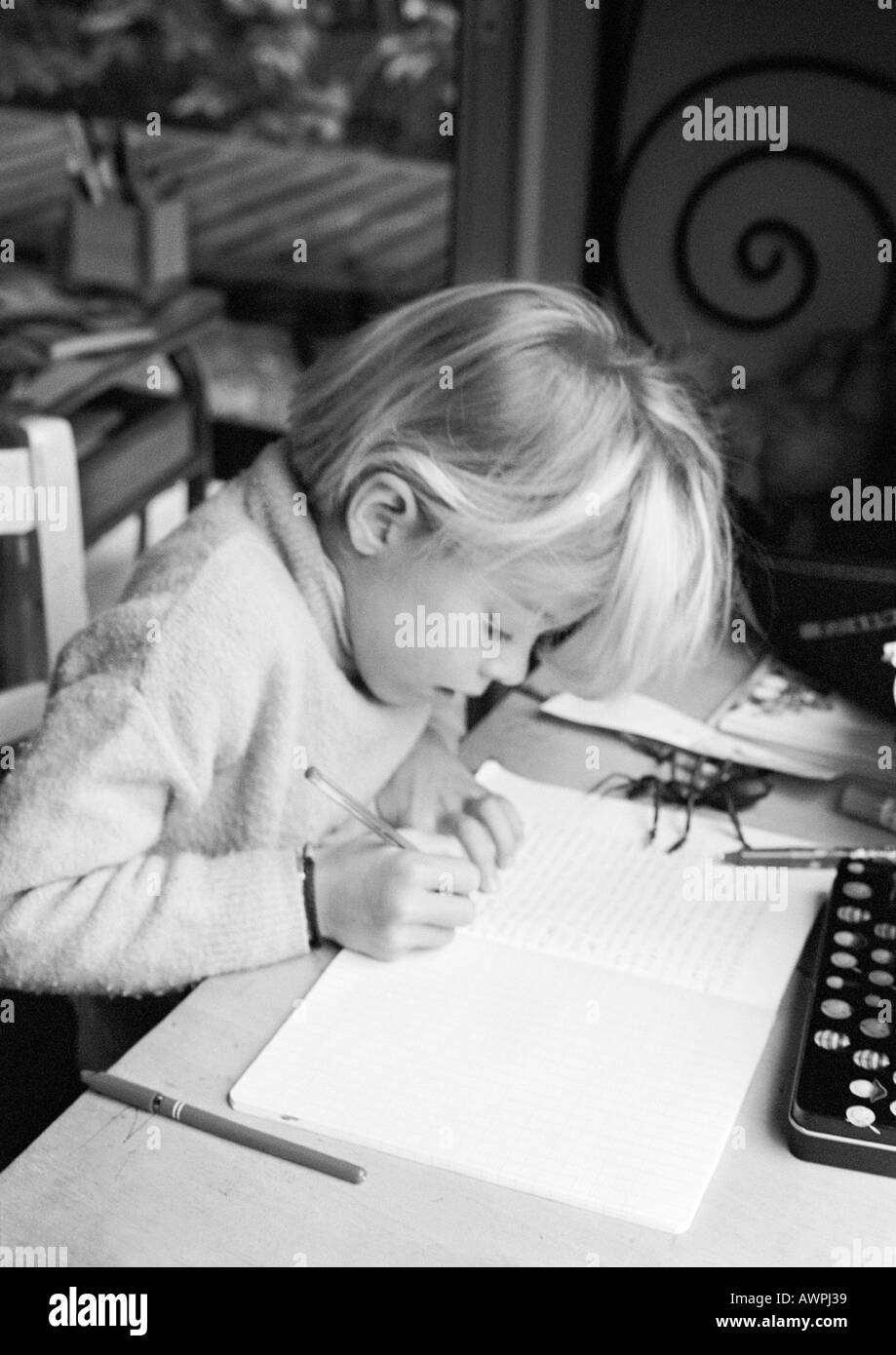 Girl sitting at desk, writing in notebook, b&w - Stock Image