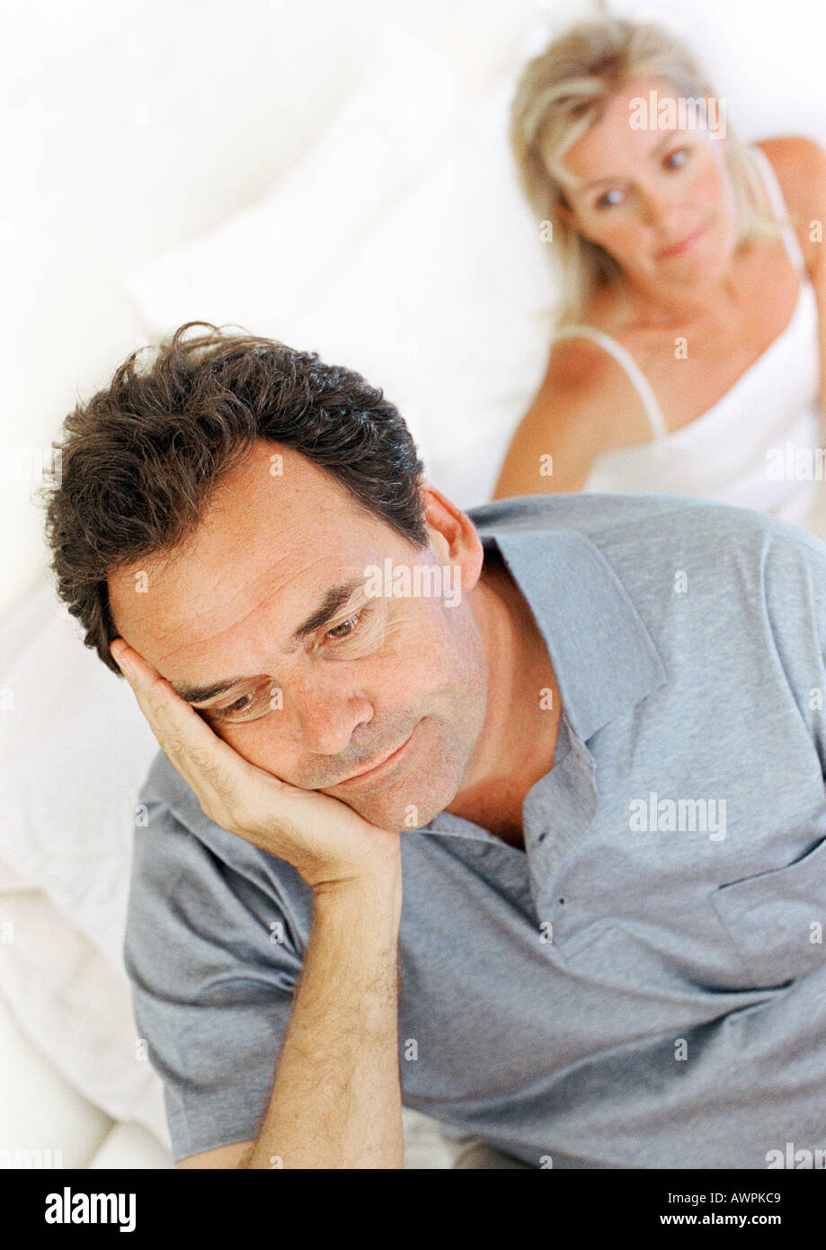 Man sitting on bed, holding head, wife in background - Stock Image