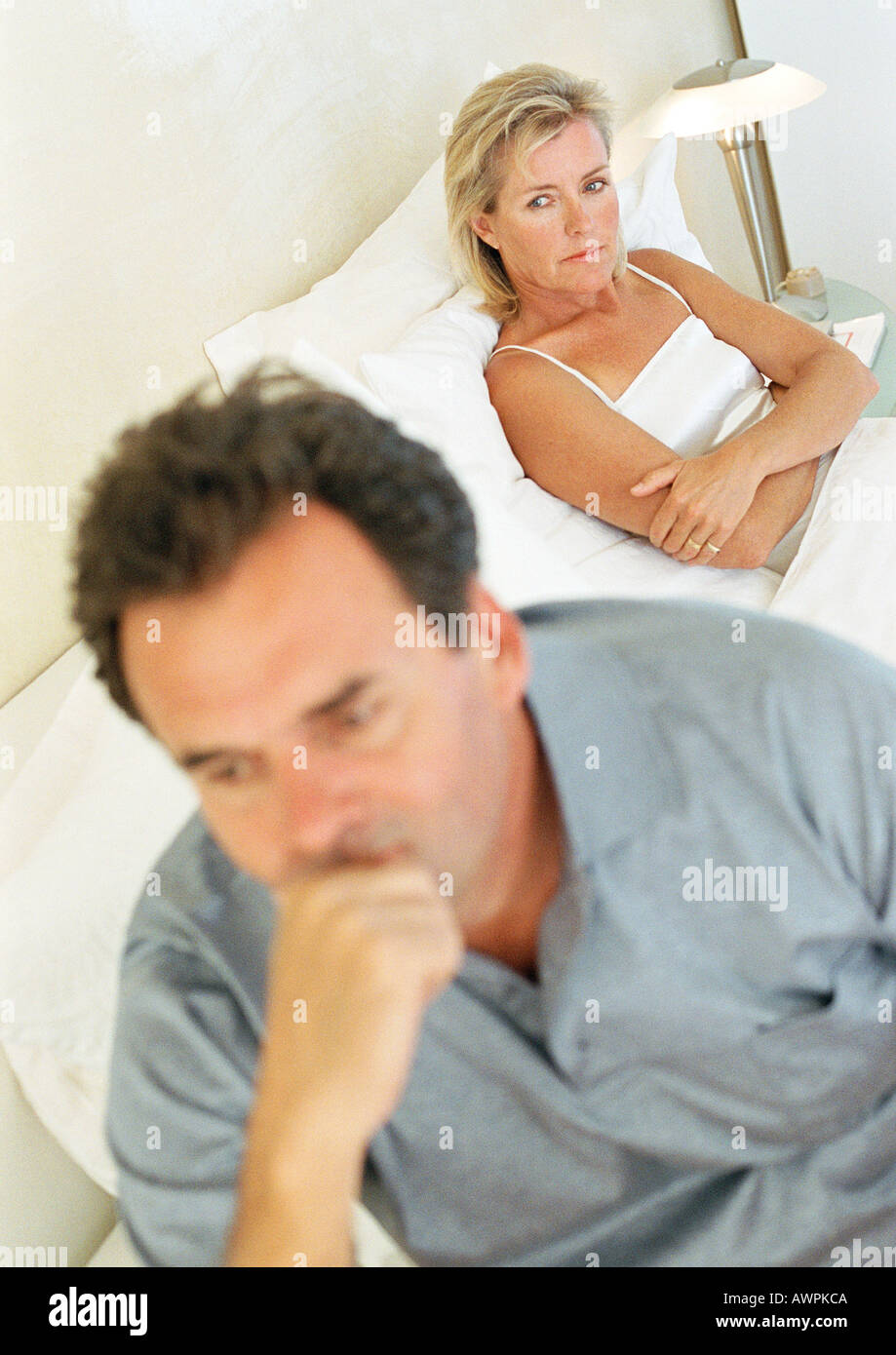 Couple in bed, woman with arms folded, man holding head - Stock Image