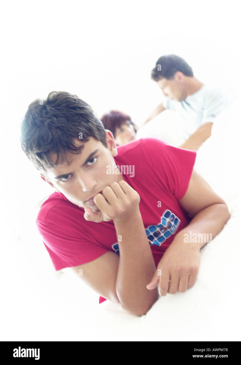 Young man with hand under chin, parents talking in background - Stock Image