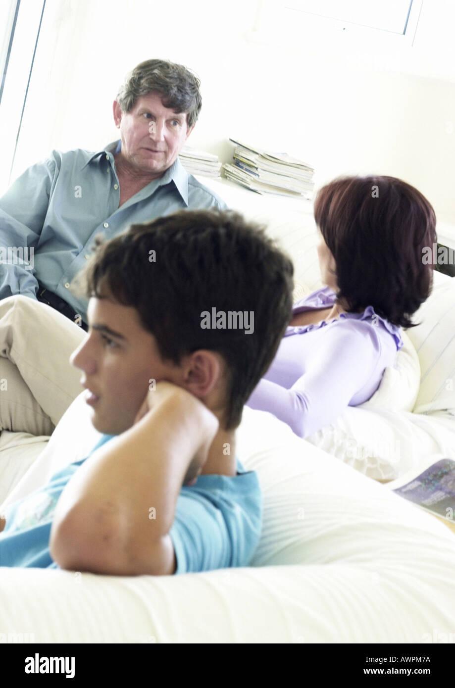 Mature couple and teenage boy sitting on sofa - Stock Image