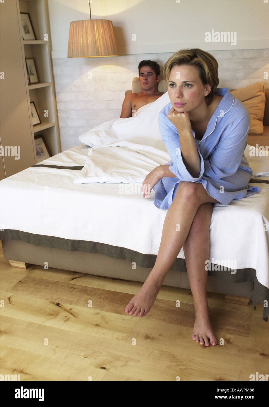 Man lying in bed, woman sitting at end of bed - Stock Image