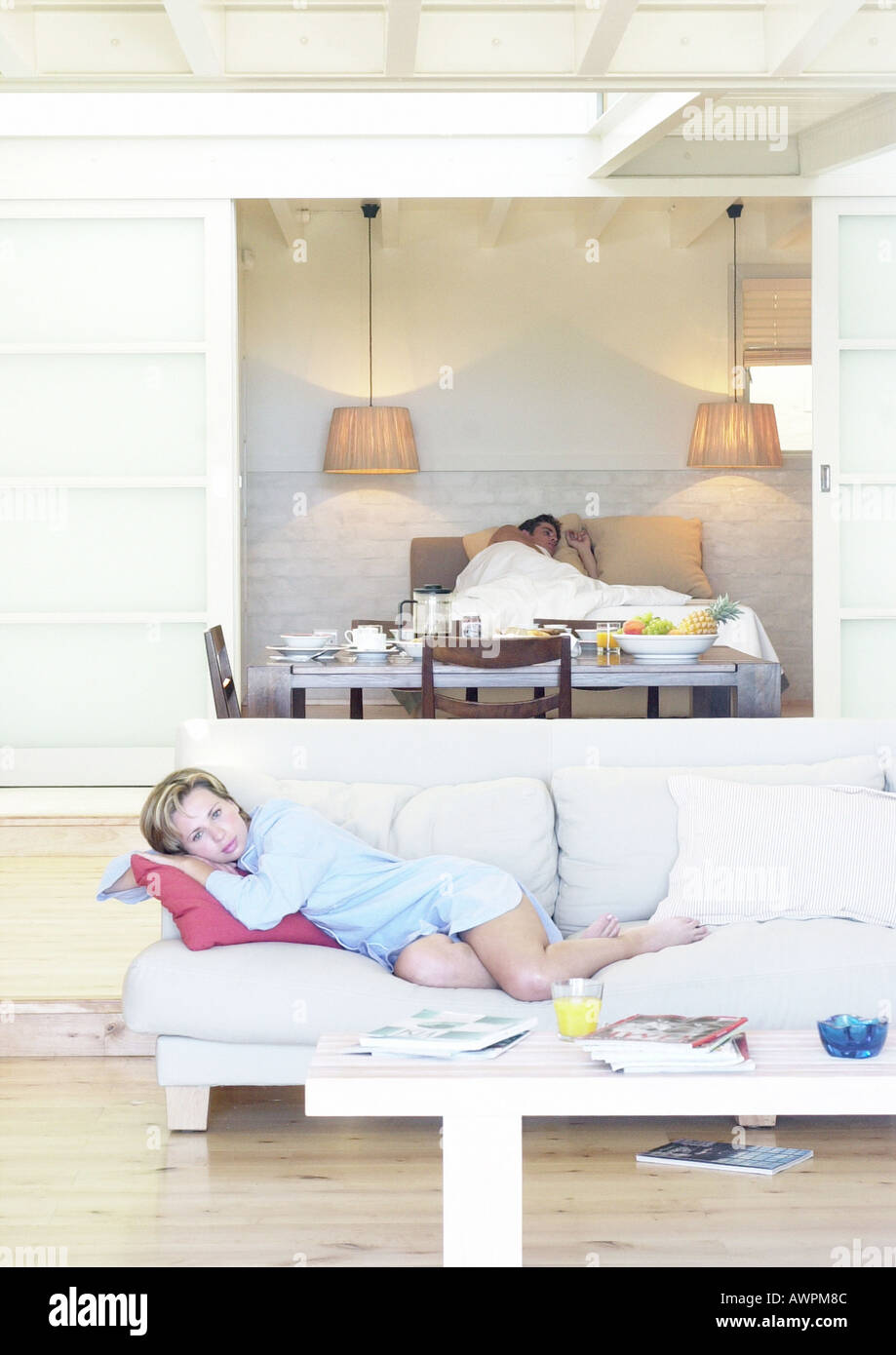 Woman lounging on sofa, man lying in bed in background - Stock Image