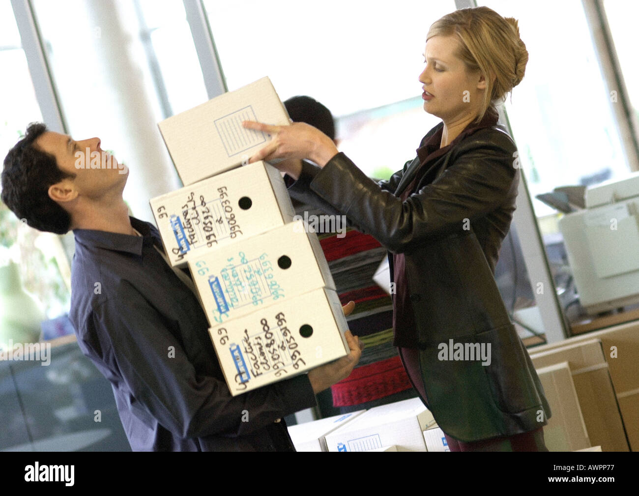 Woman piling boxes up in man's arms, side view - Stock Image