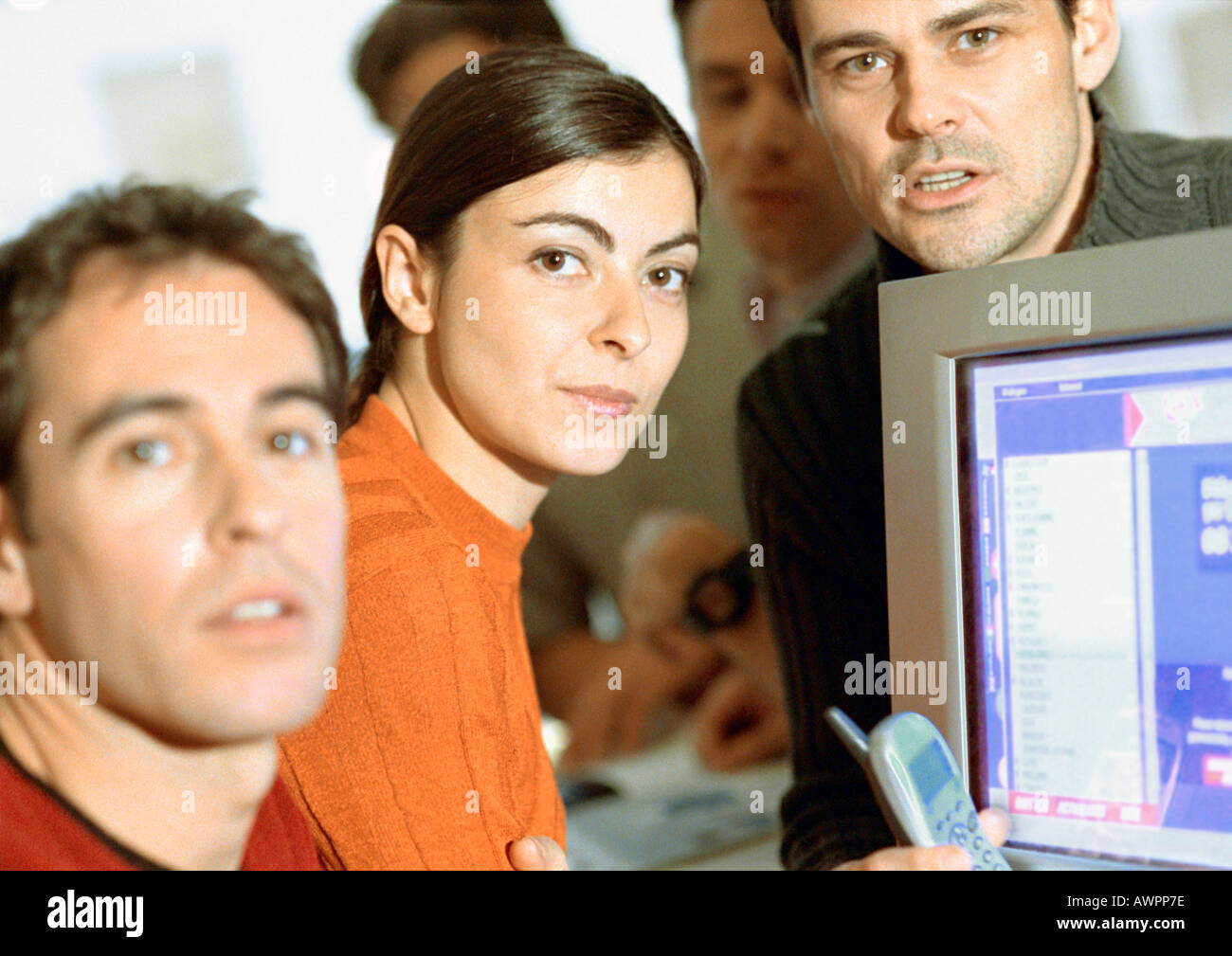 Adults grouped around computer, close-up - Stock Image