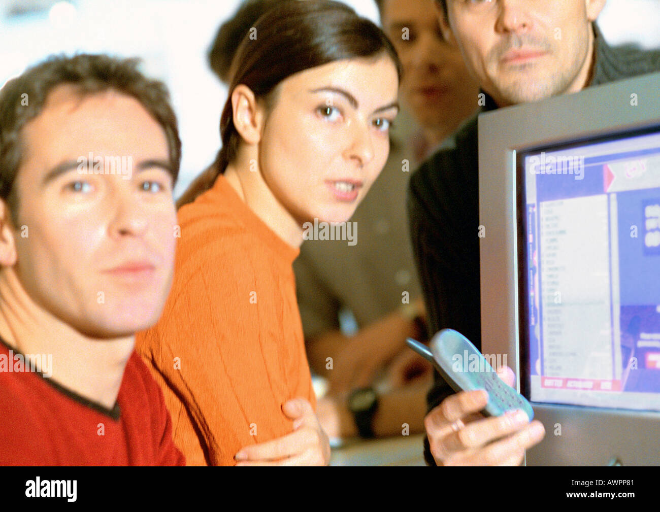 Adults grouped around computer screen, close-up, looking at camera - Stock Image