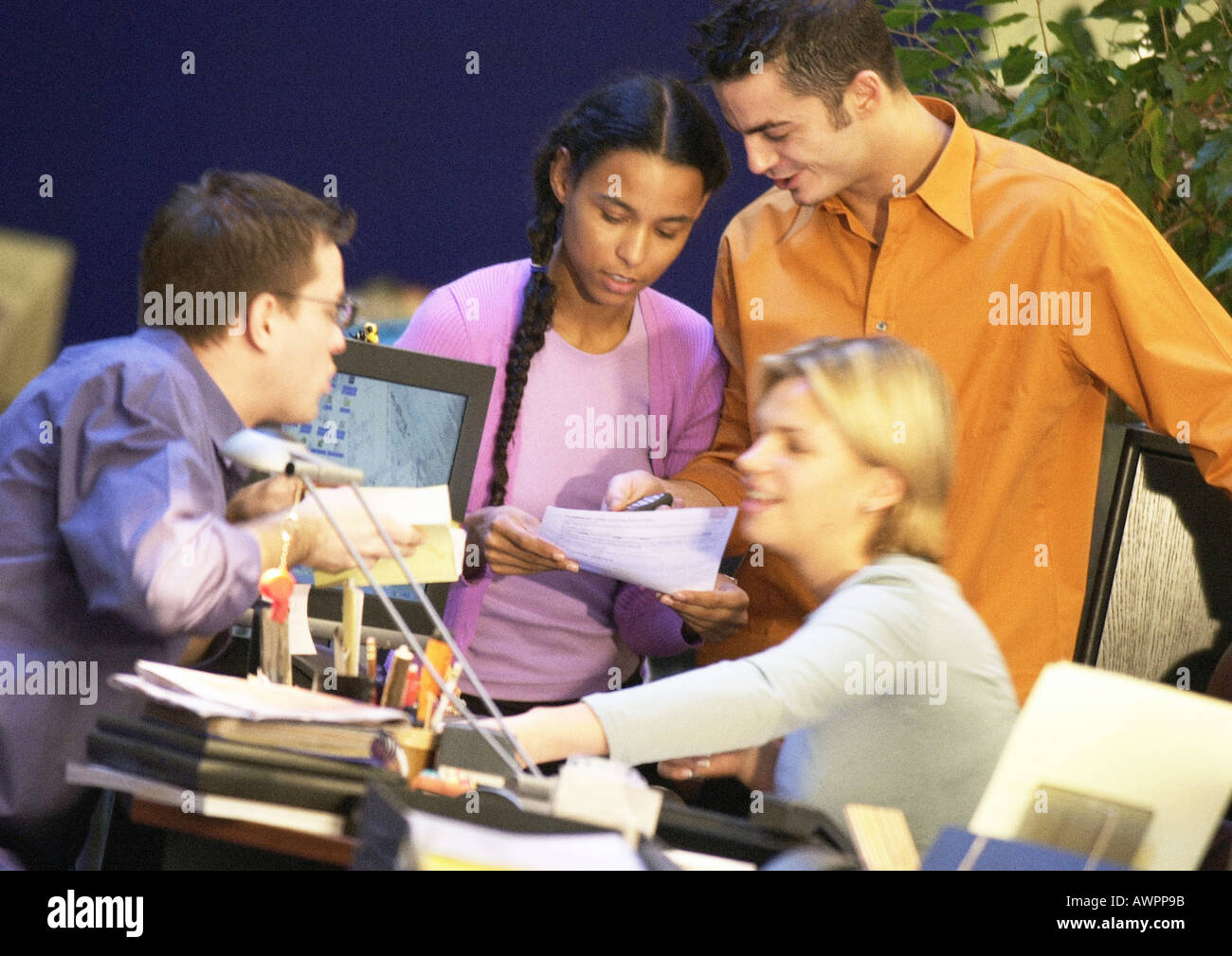 Four people interacting in office, close-up - Stock Image