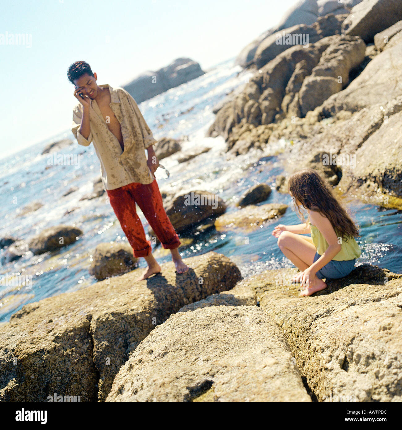 Teenager using cell phone, child sitting on rock - Stock Image
