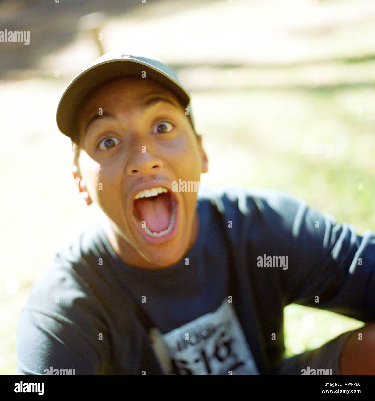 Teenage boy opening mouth, portrait - Stock Image