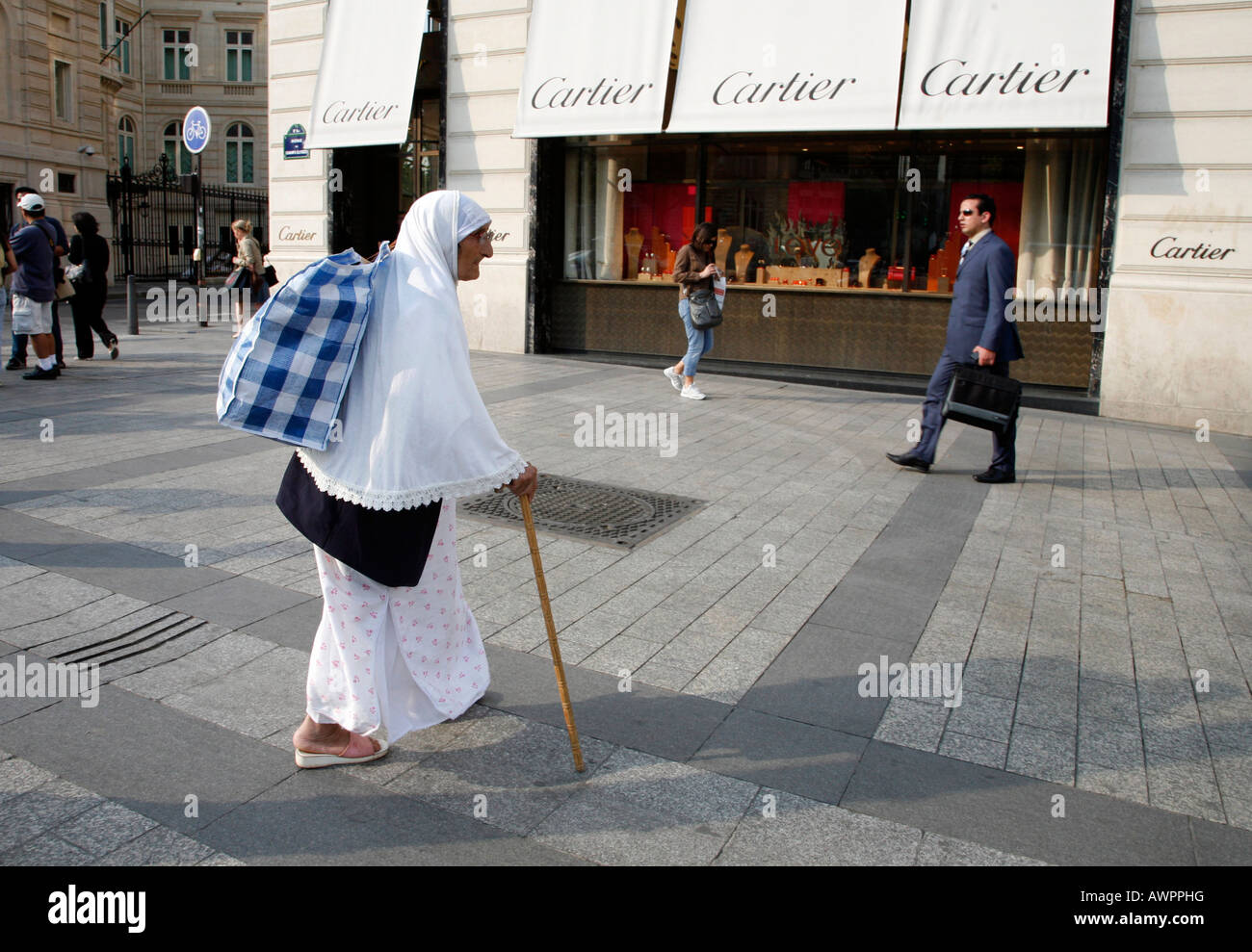 Beggar in front of the Cartier boutique on Avenue des Champs Elysées in Paris, France, Europe - Stock Image