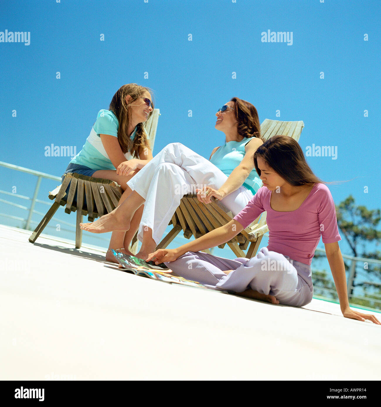 Mother and daughters sitting outside - Stock Image