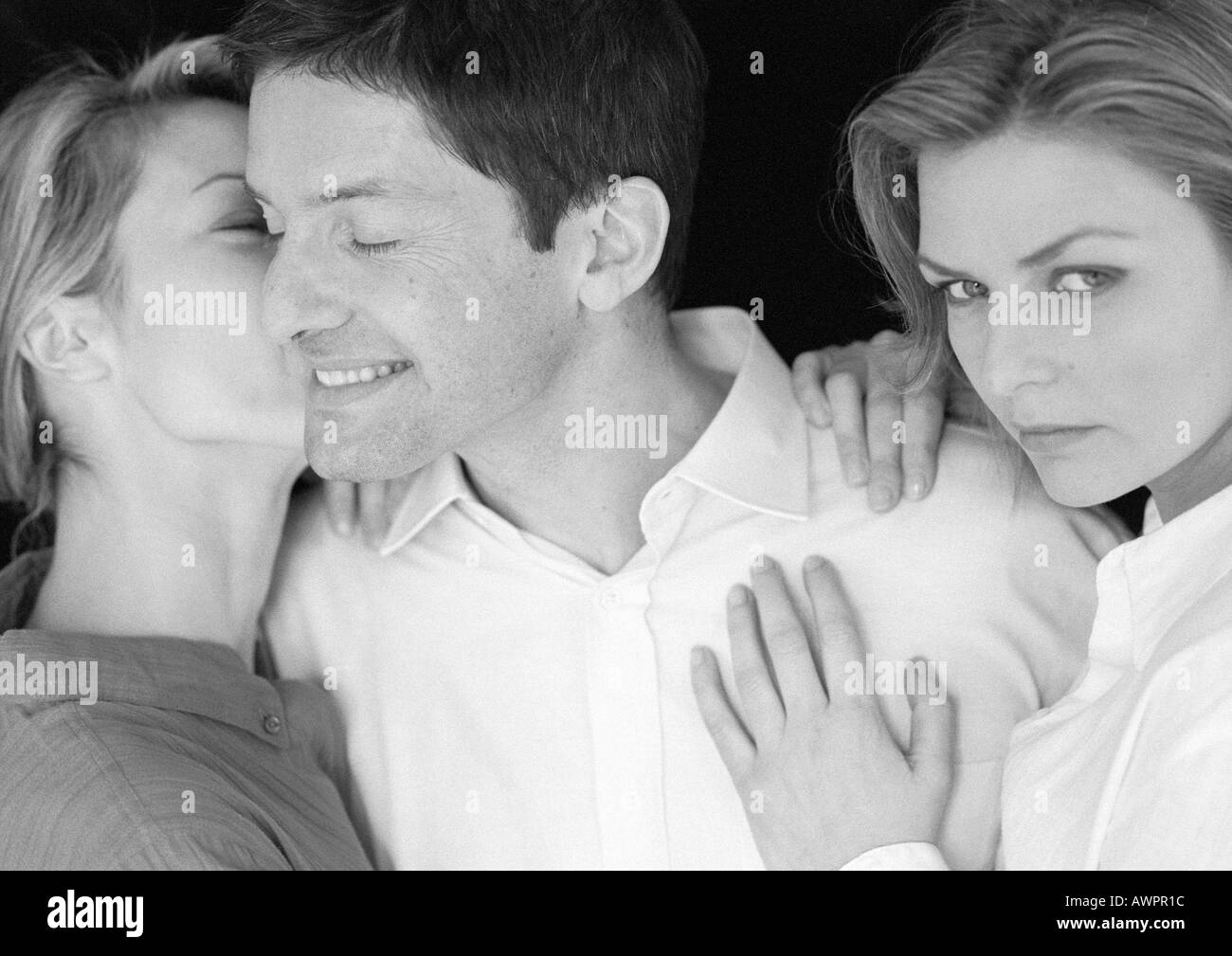 Man standing between two women, being kissed by one, b&w - Stock Image