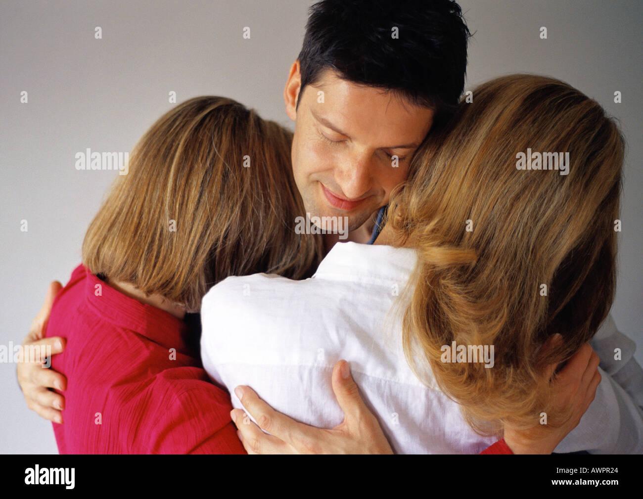 Man hugging two women, eyes closed - Stock Image