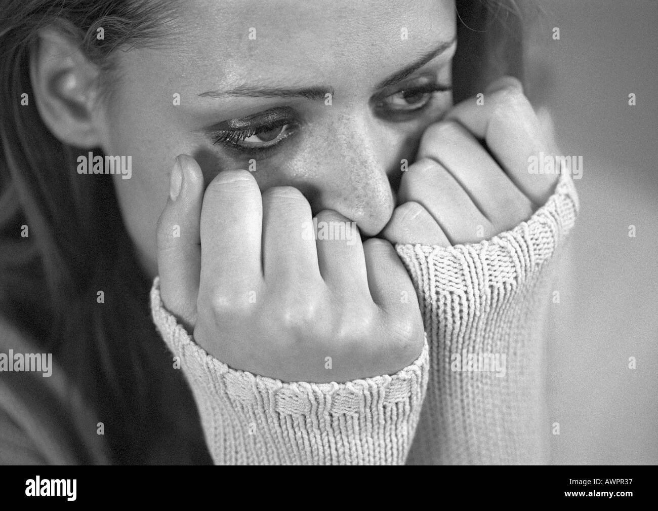 Woman with hands covering lower face, close-up, b&w - Stock Image