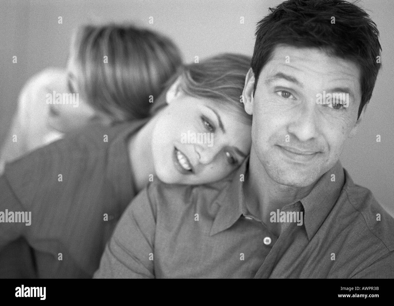 Woman leaning on man's shoulder, second woman leaning on her shoulder, b&w - Stock Image