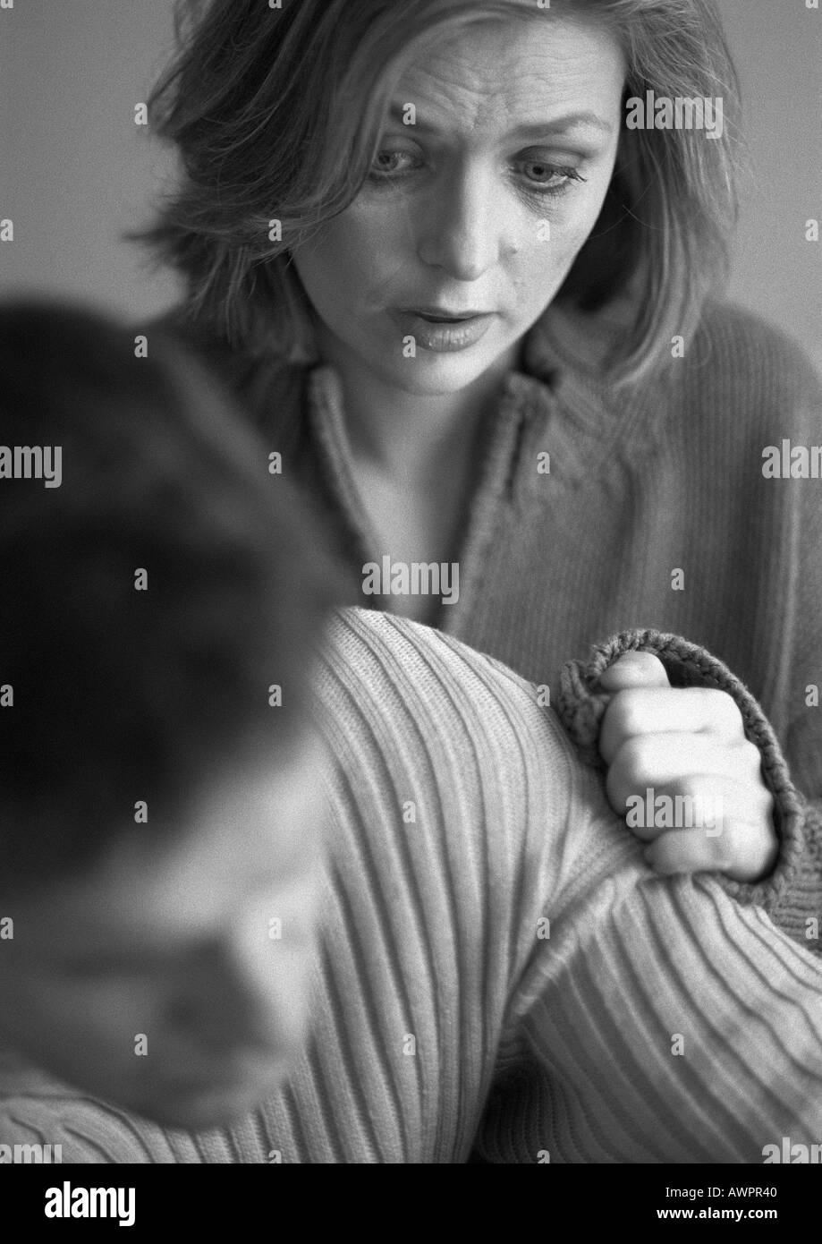 Woman touching man's arm, close-up, b&w - Stock Image