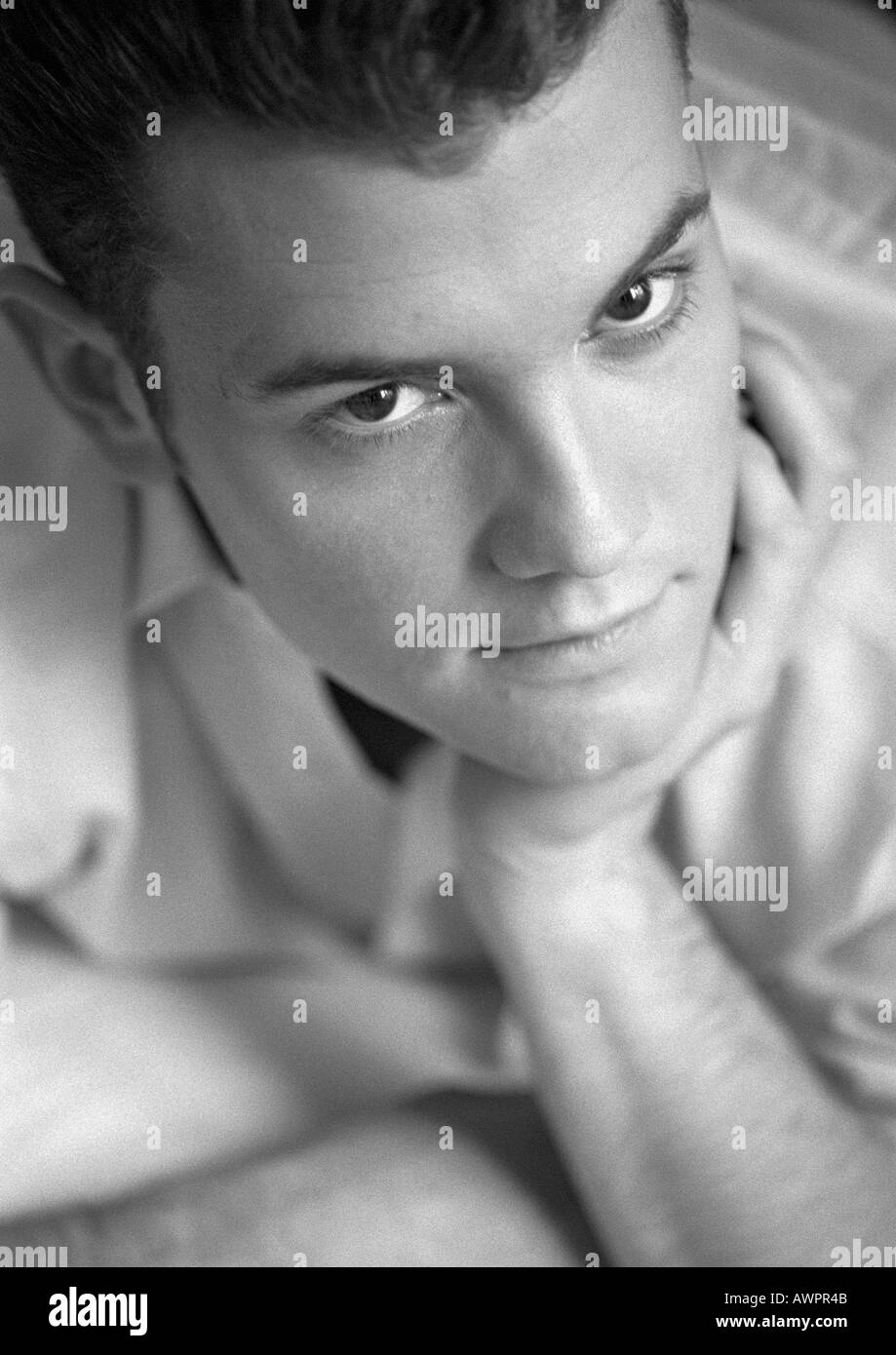 Man leaning on elbow, close-up, b&w - Stock Image