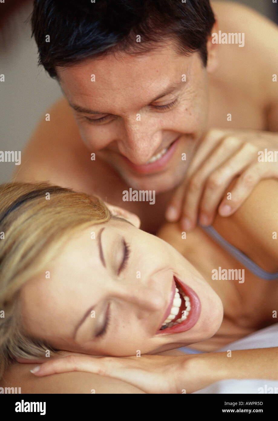 Couple lying on bed, smiling - Stock Image