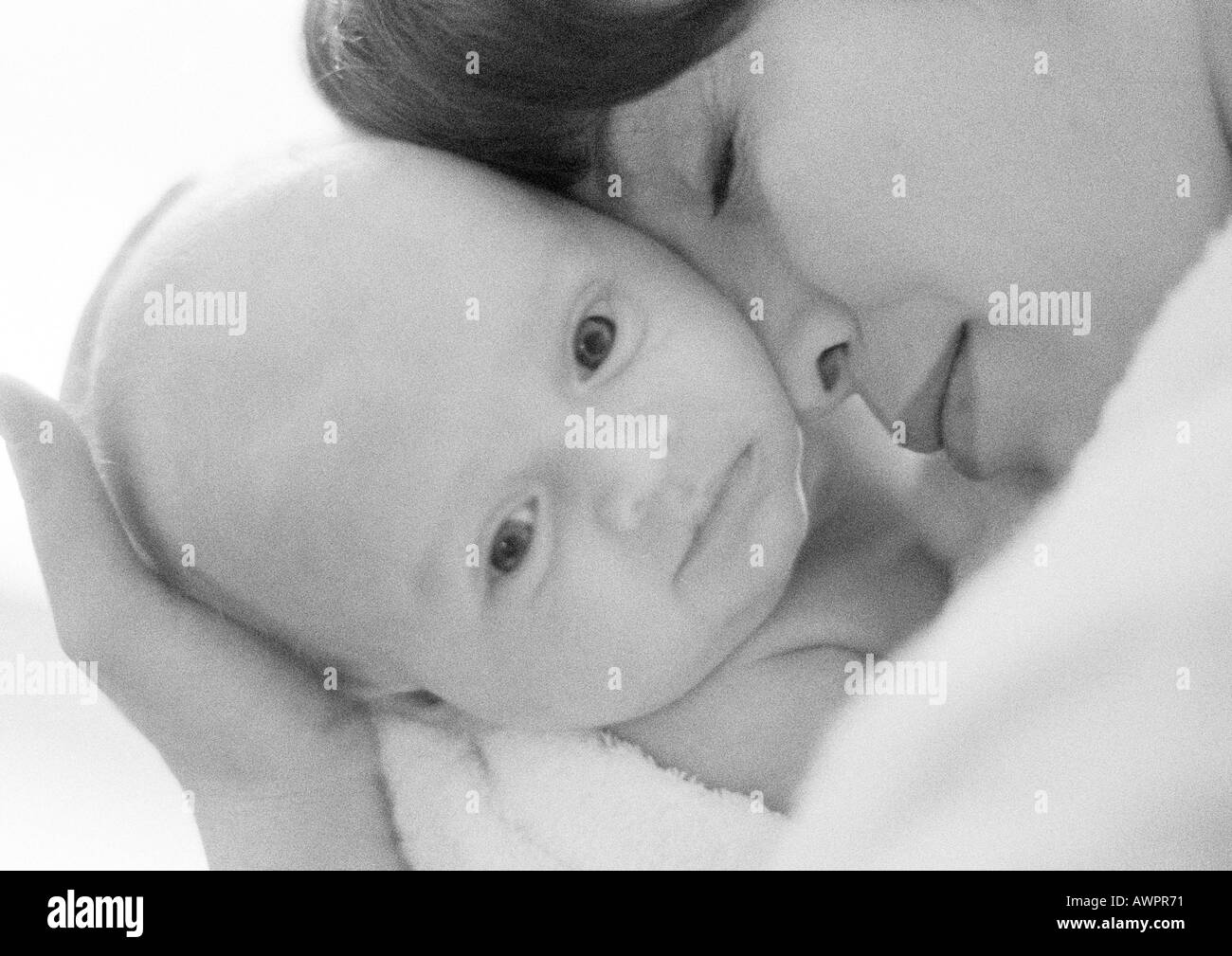 Mother holding infant against face, close-up, b&w - Stock Image
