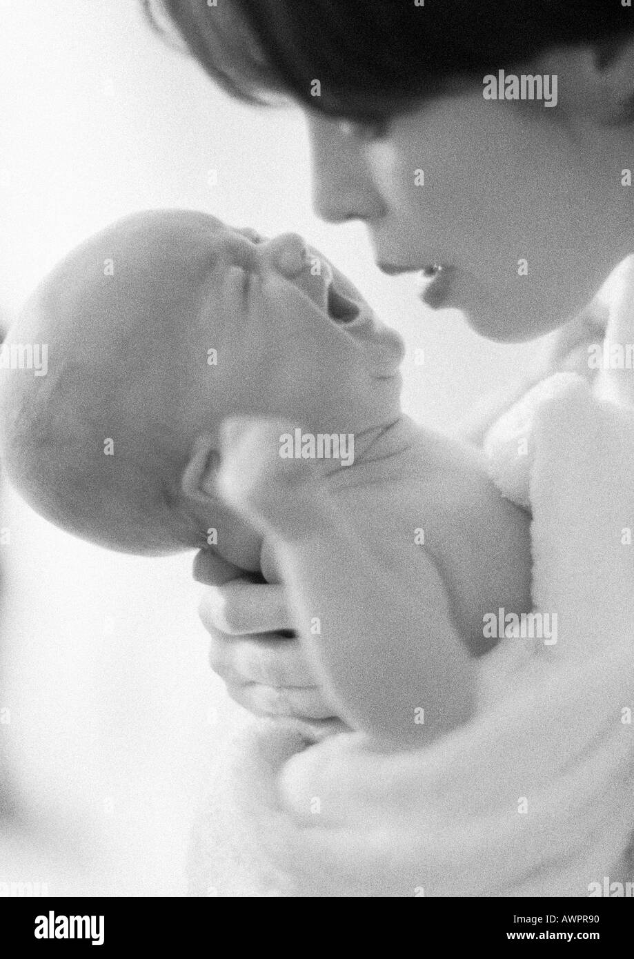 Mother holding crying infant, b&w - Stock Image