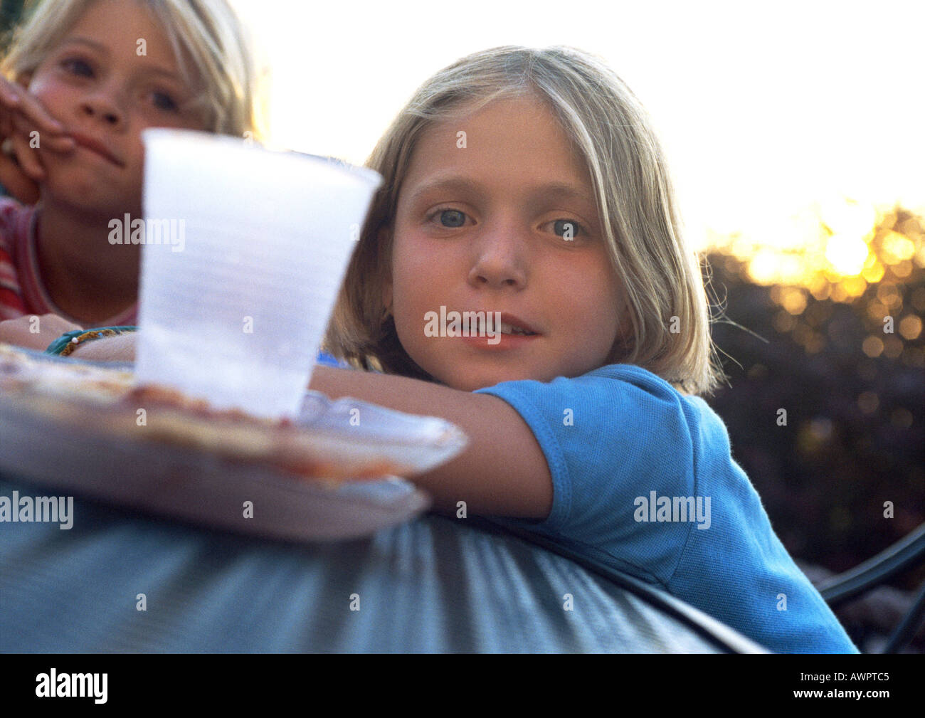 Two Girls Sitting At Table Plastic Cup In Foreground