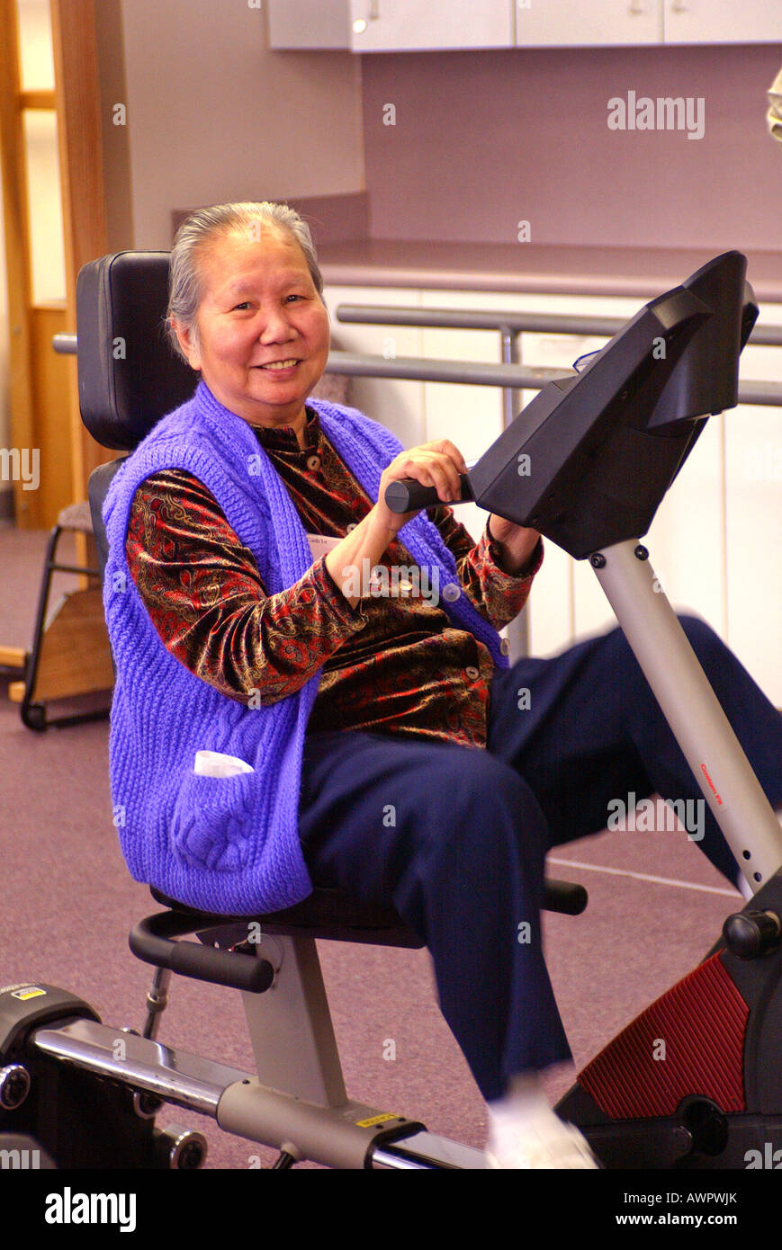 Asian American senior exercises with pedal machine at senior day care  center Garden Grove California USA Model released