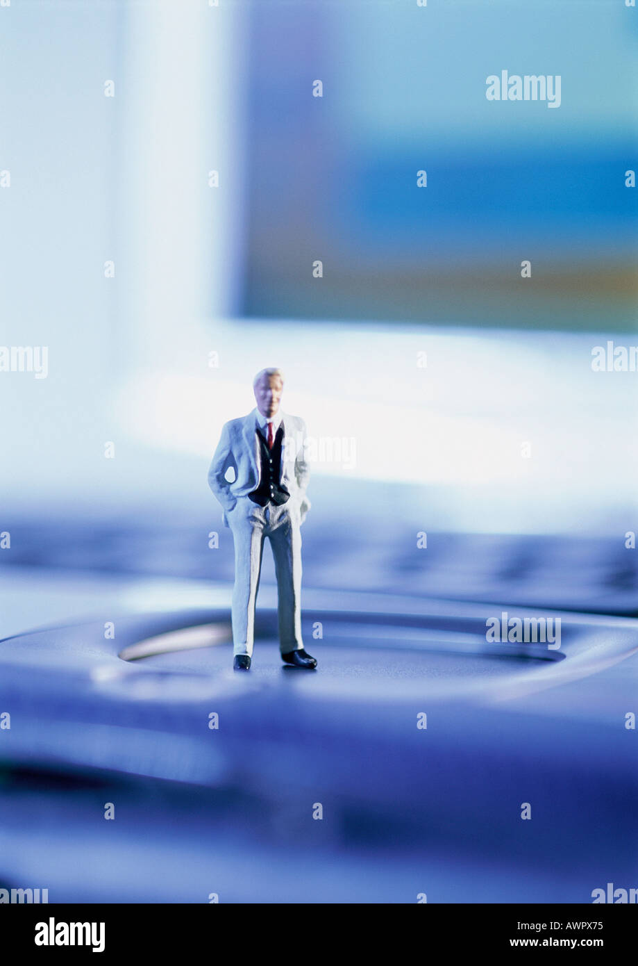 Small toy figure standing on computer keyboard, focus on figure - Stock Image
