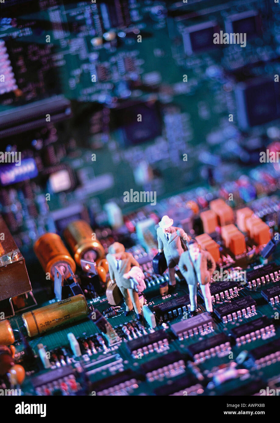 Toy figures on computer circuit board, close-up - Stock Image