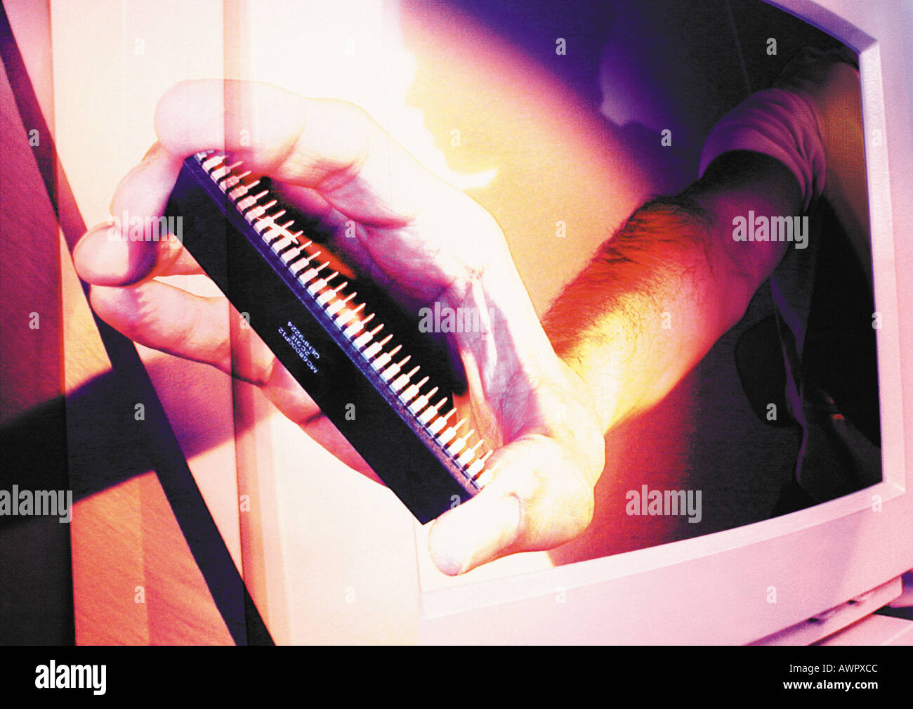 Hand emerging from computer monitor, holding circuit board, digital composite. - Stock Image