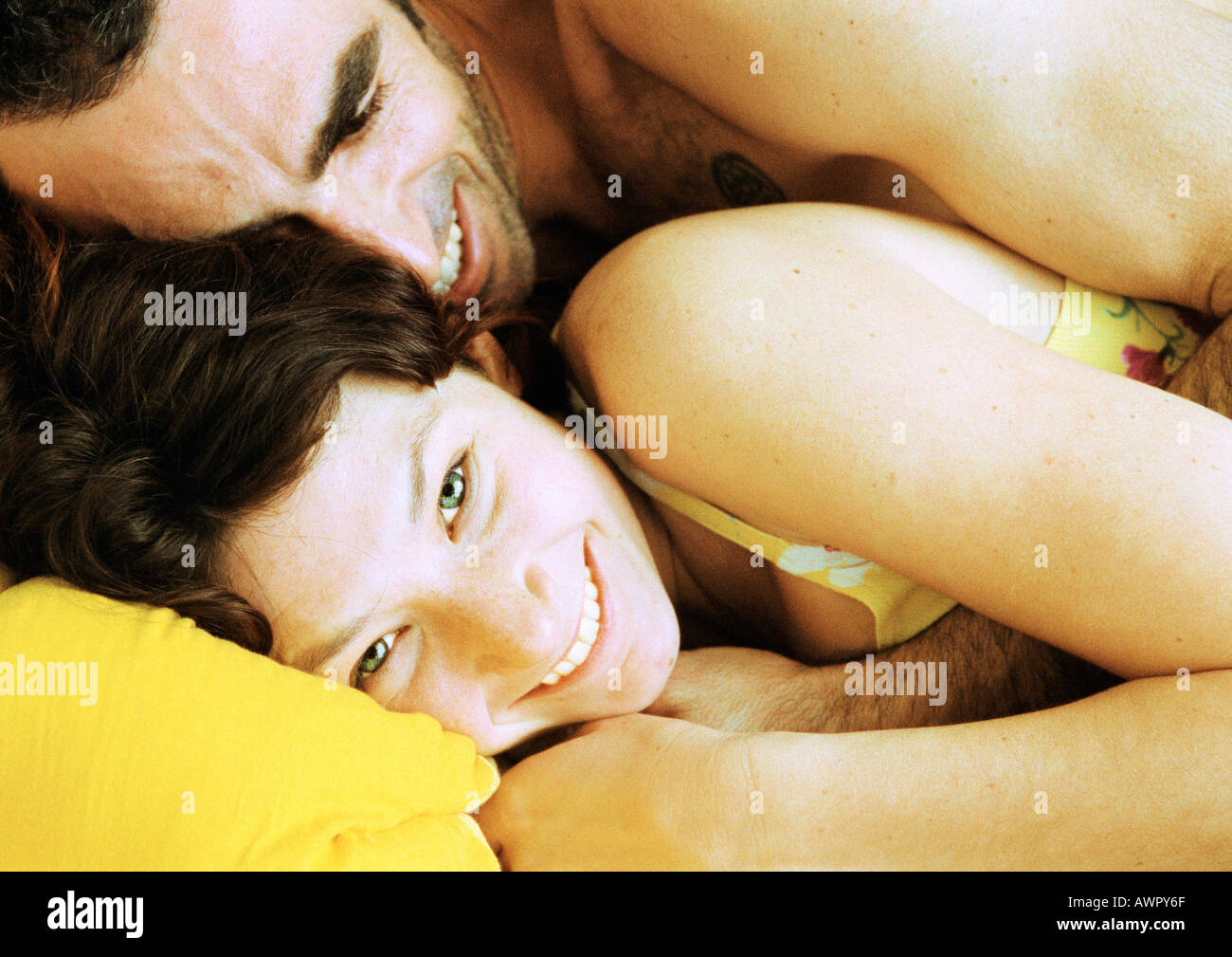 Couple in bed, man lying on woman's back, close-up. Stock Photo