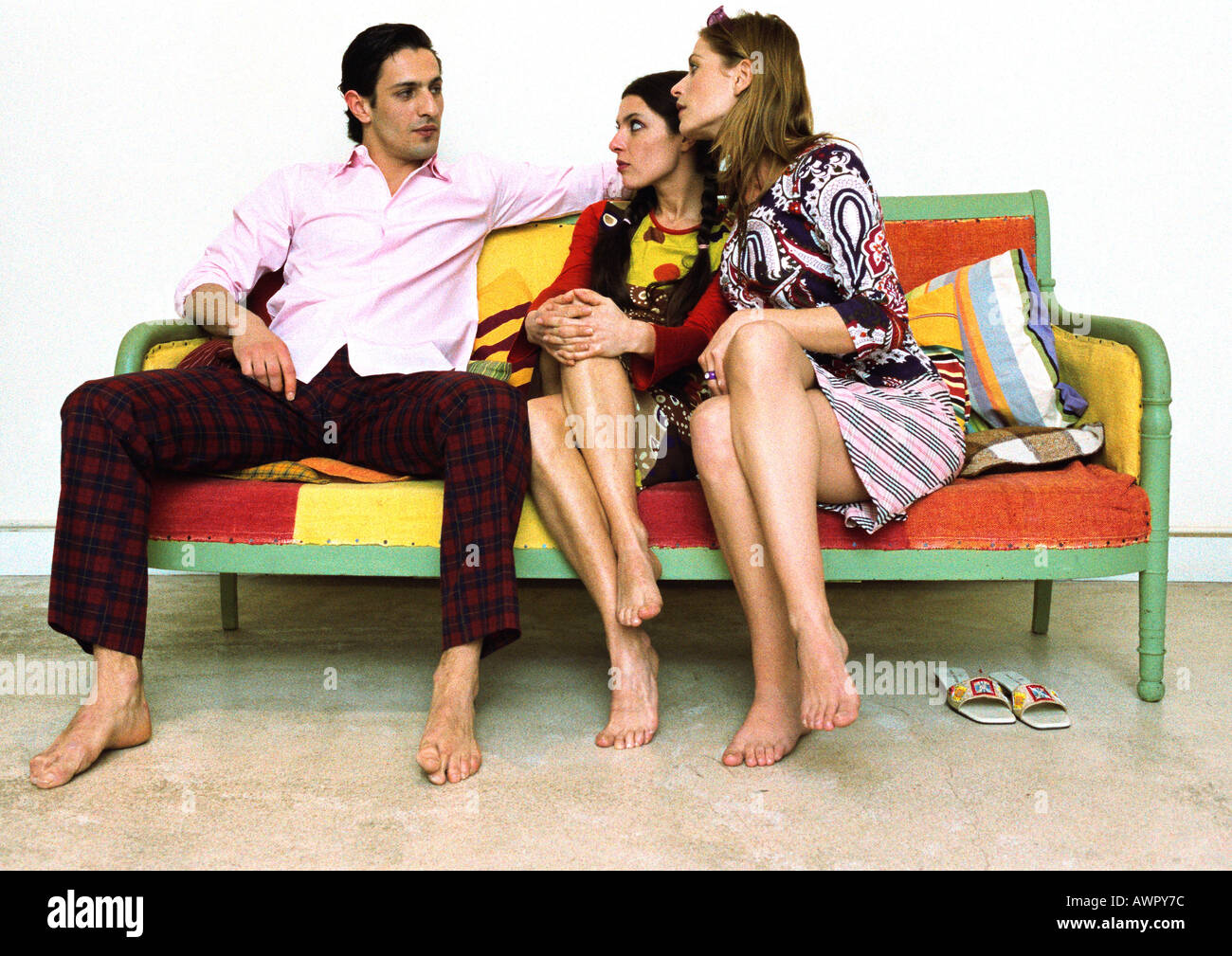 Man sitting on sofa with legs apart looking at two women sitting next to him with legs crossed Stock Photo