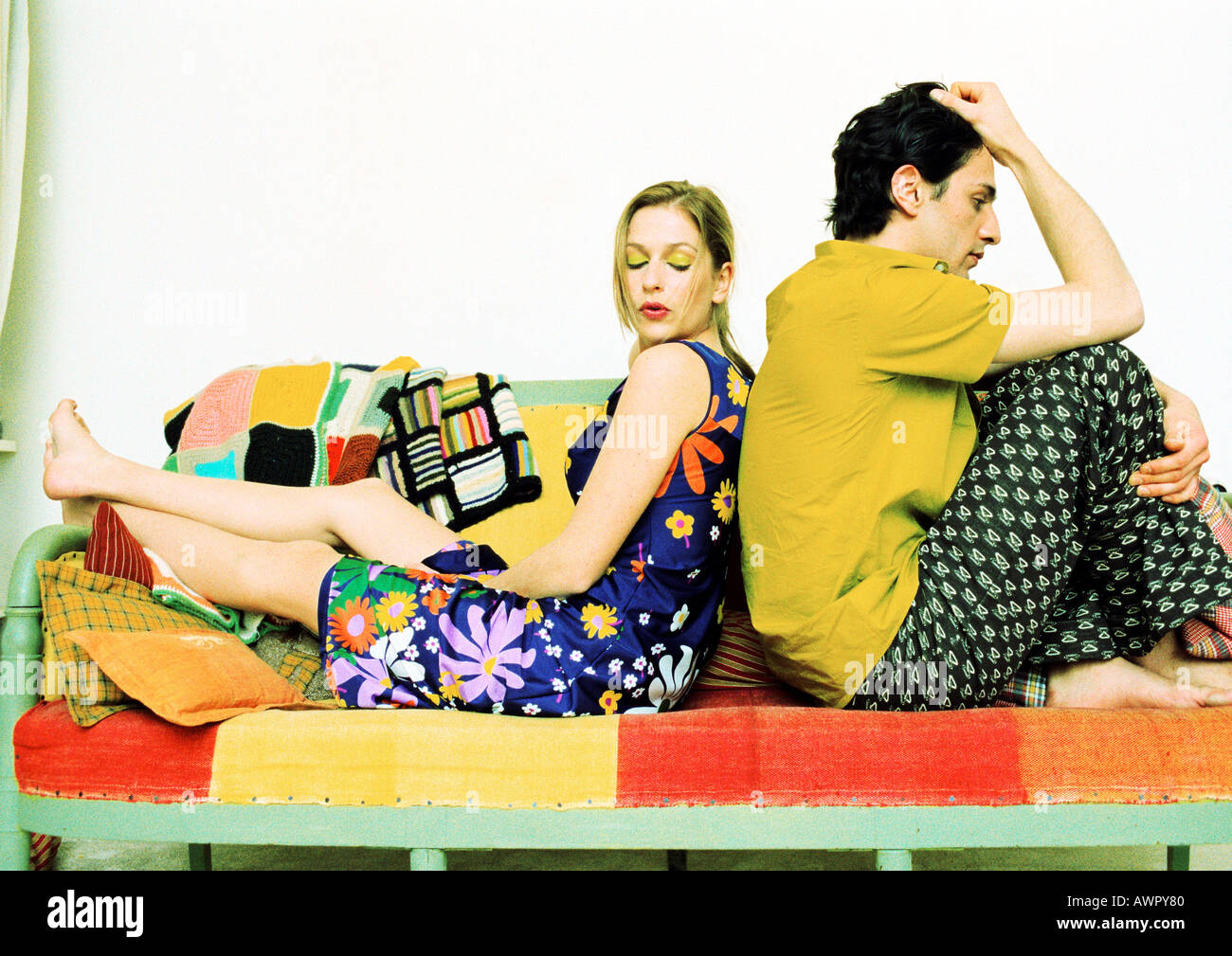 Couple sitting on sofa, back to back. - Stock Image