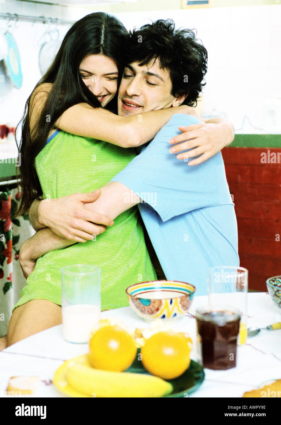 Couple hugging in front of breakfast table, portrait. Stock Photo