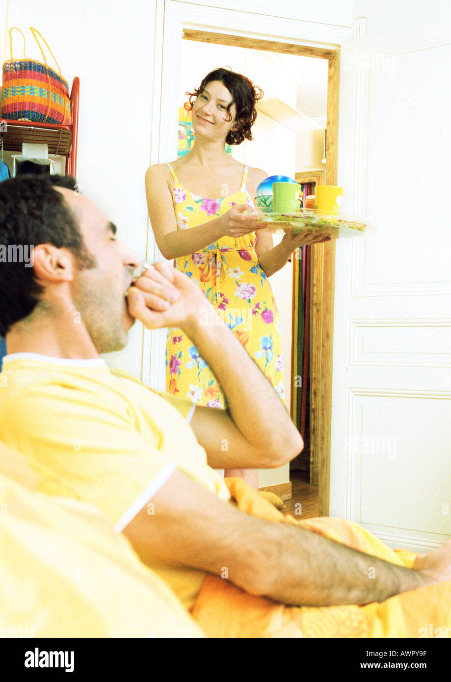 Man in bed yawning, woman carrying breakfast tray. - Stock Image
