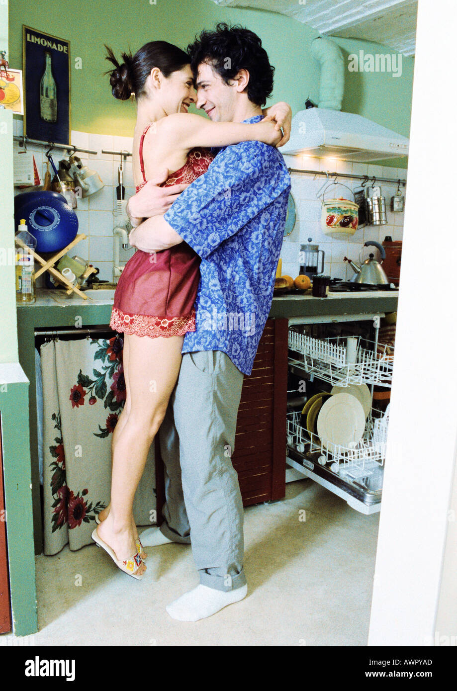 Man and woman embracing in kitchen, woman's feet off the ground. Stock Photo