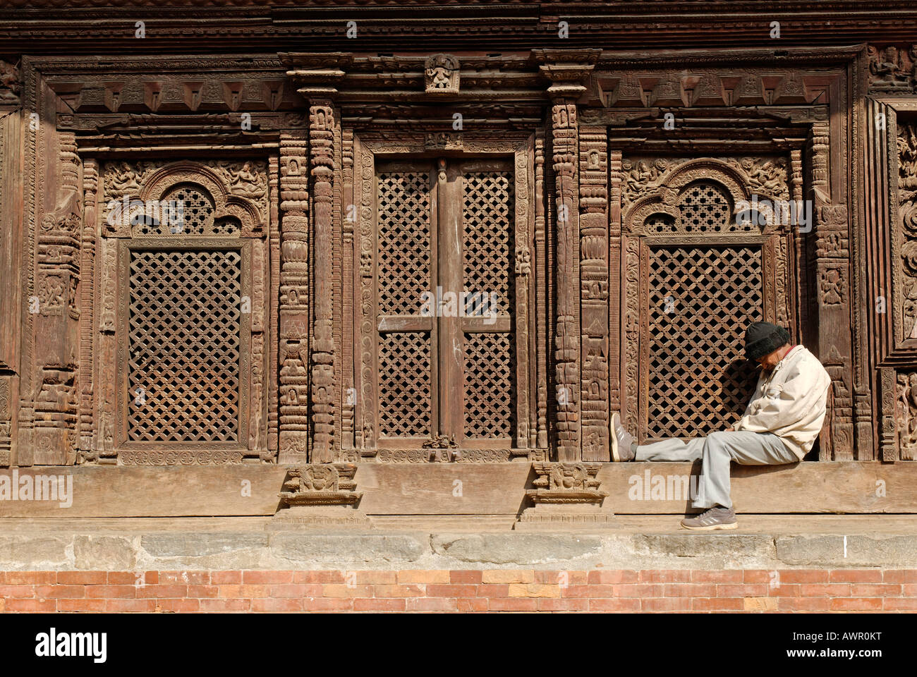 Man sleeping in front of a temple, Durbar Square of Patan, Lalitpur, Kathmandu, Nepal - Stock Image