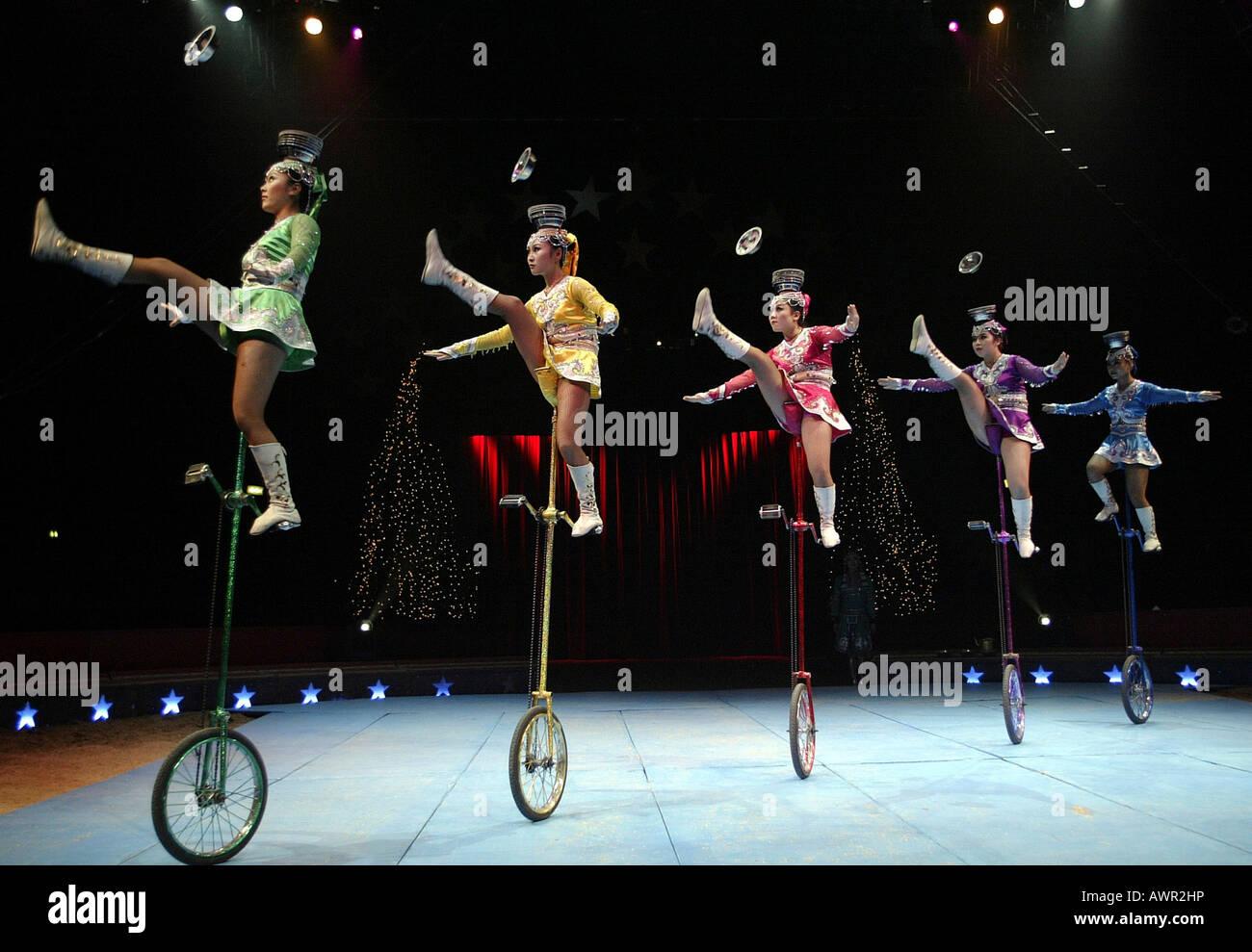 Five chinese artists juggle on unicycles. Stuttgart, Baden-Wuerttemberg, Germany. - Stock Image