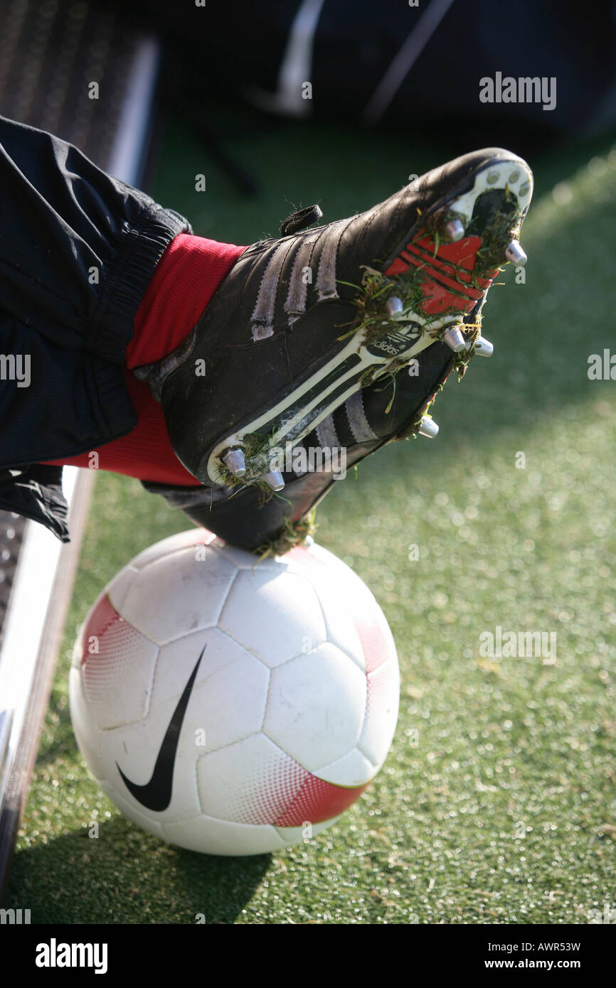 Sports shoes on a soccer ball - Stock Image