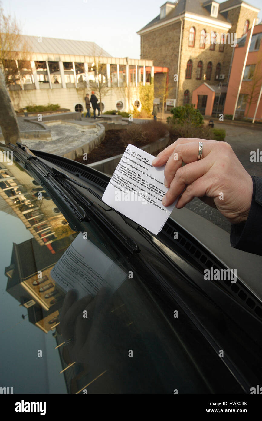 Traffic warden put a fine on the front shield Stock Photo