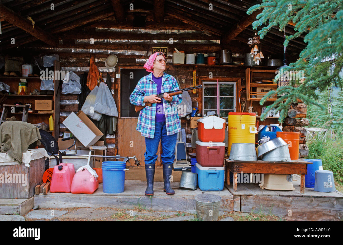 Armed woman standing in front of her log home, Brooks Range, Alaska, USA - Stock Image
