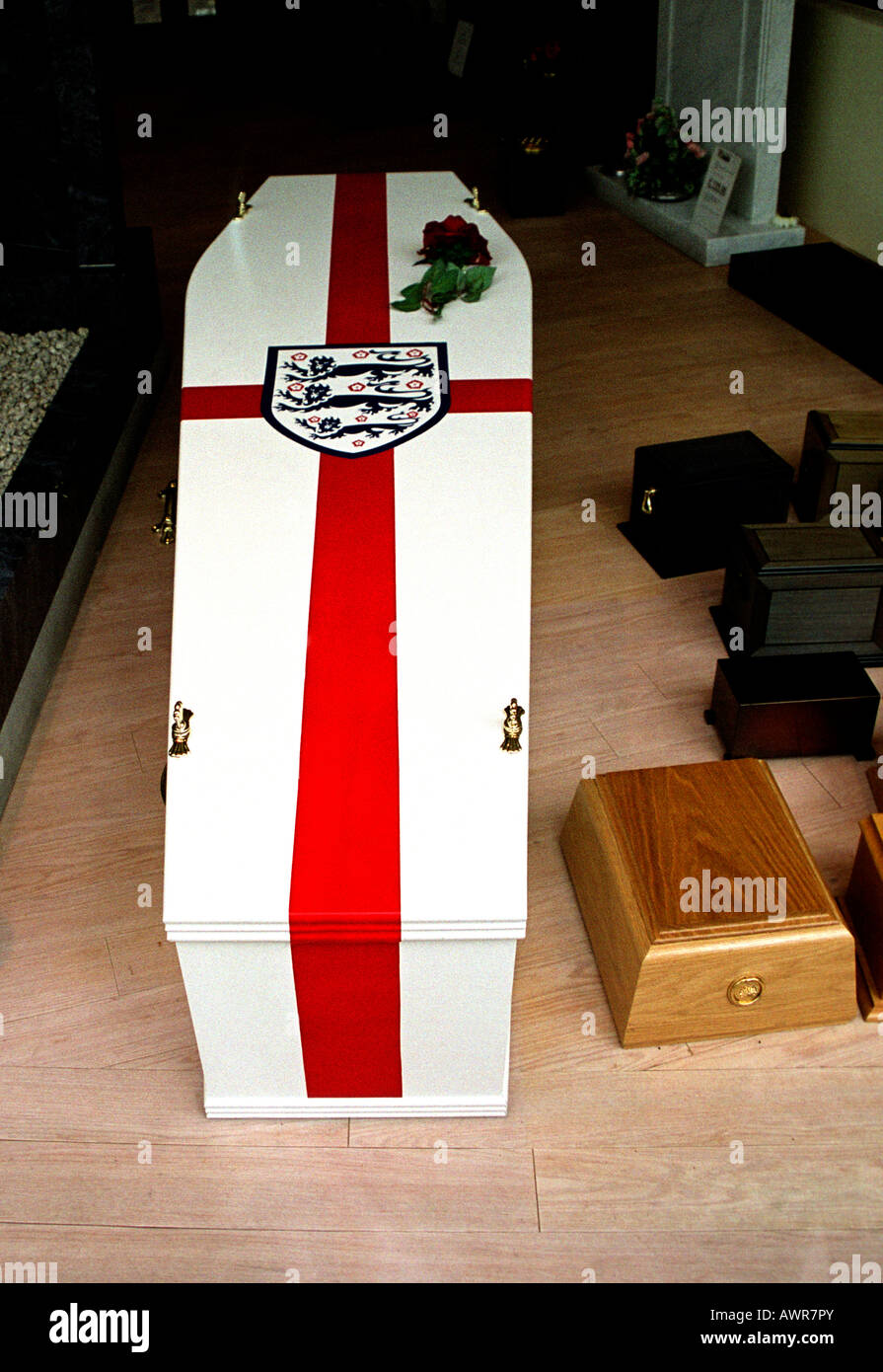 Coffin in undertakers showroom finished in colours of England national flag for a die hard football fan London - Stock Image