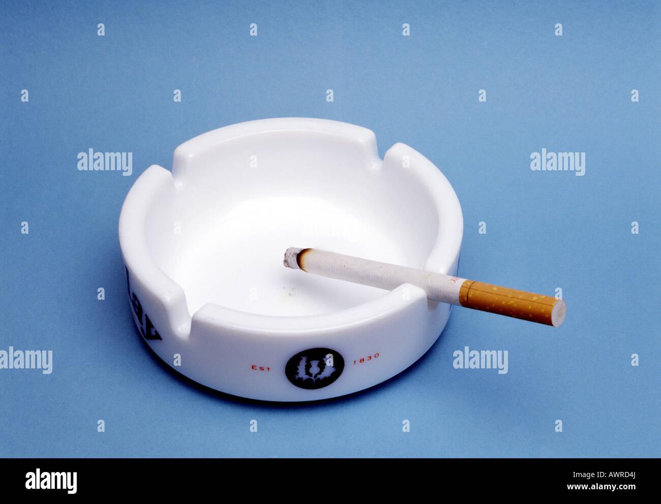 Burning cigarette in ashtray - Stock Image