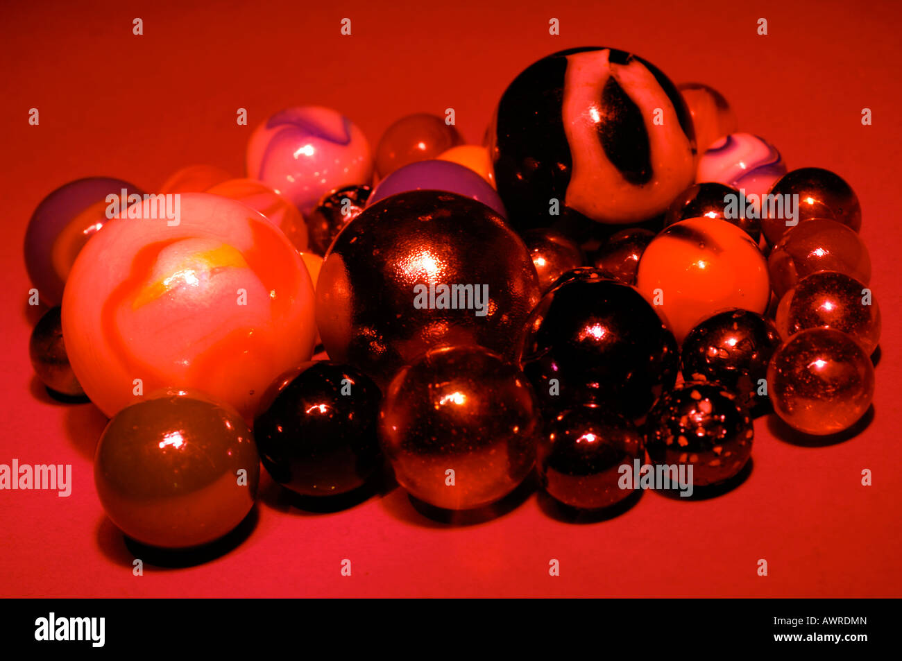a group collection of childrens marbles on against a red background - Stock Image